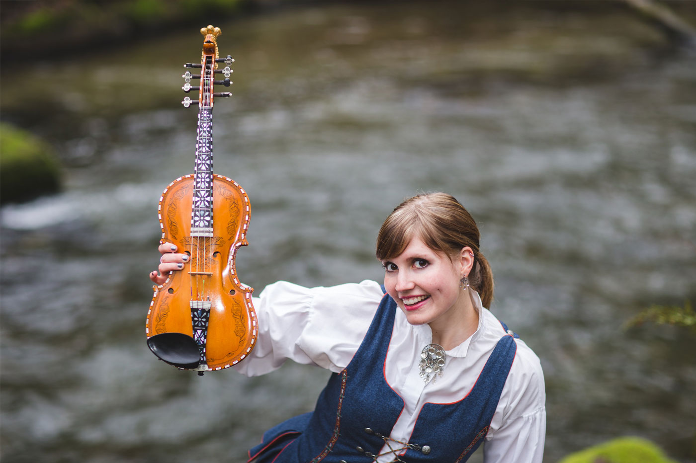 Rachel Nesvig in a traditional bunad playing Hardanger fiddle