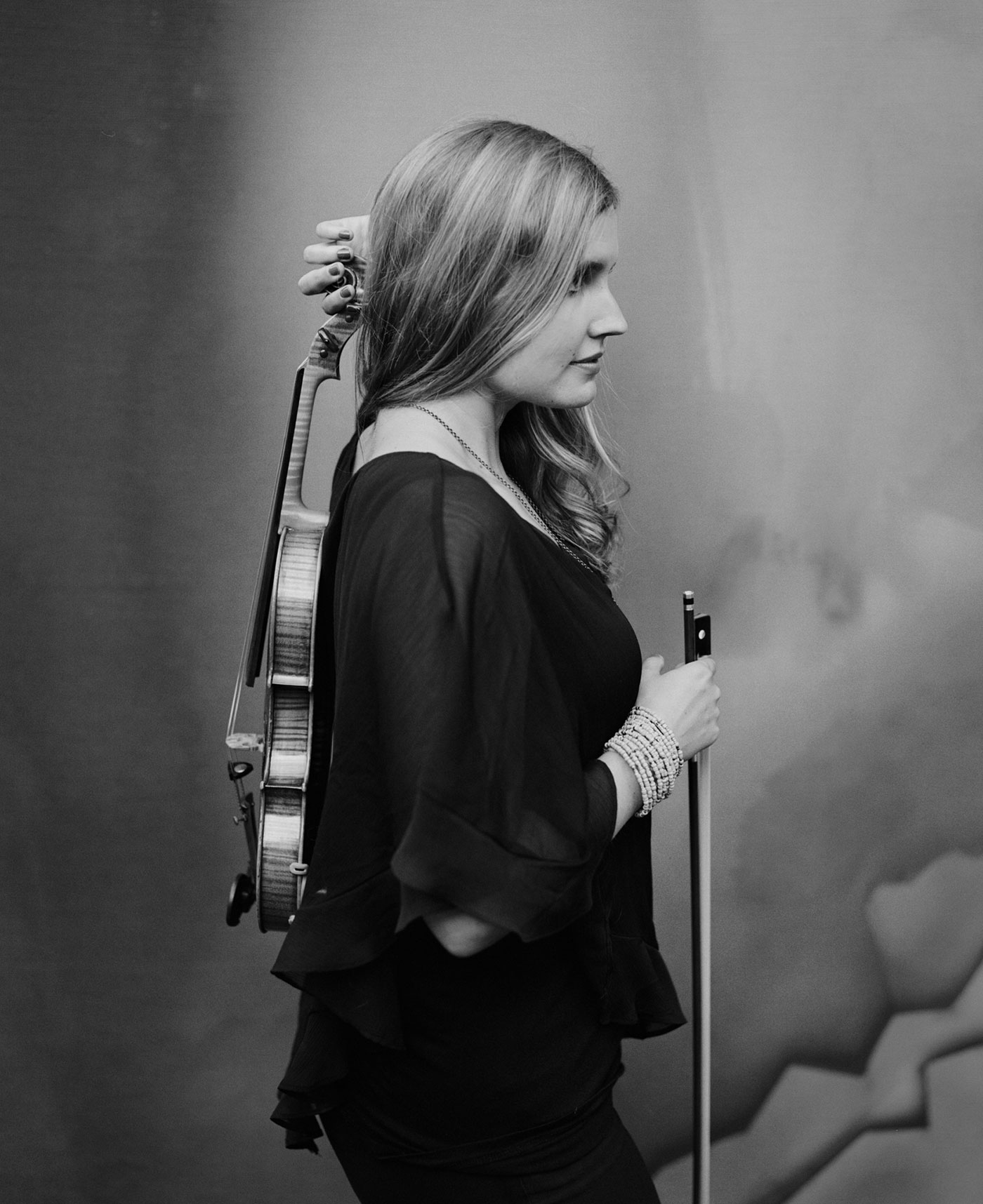 Rachel Nesvig holding a violin behind her back