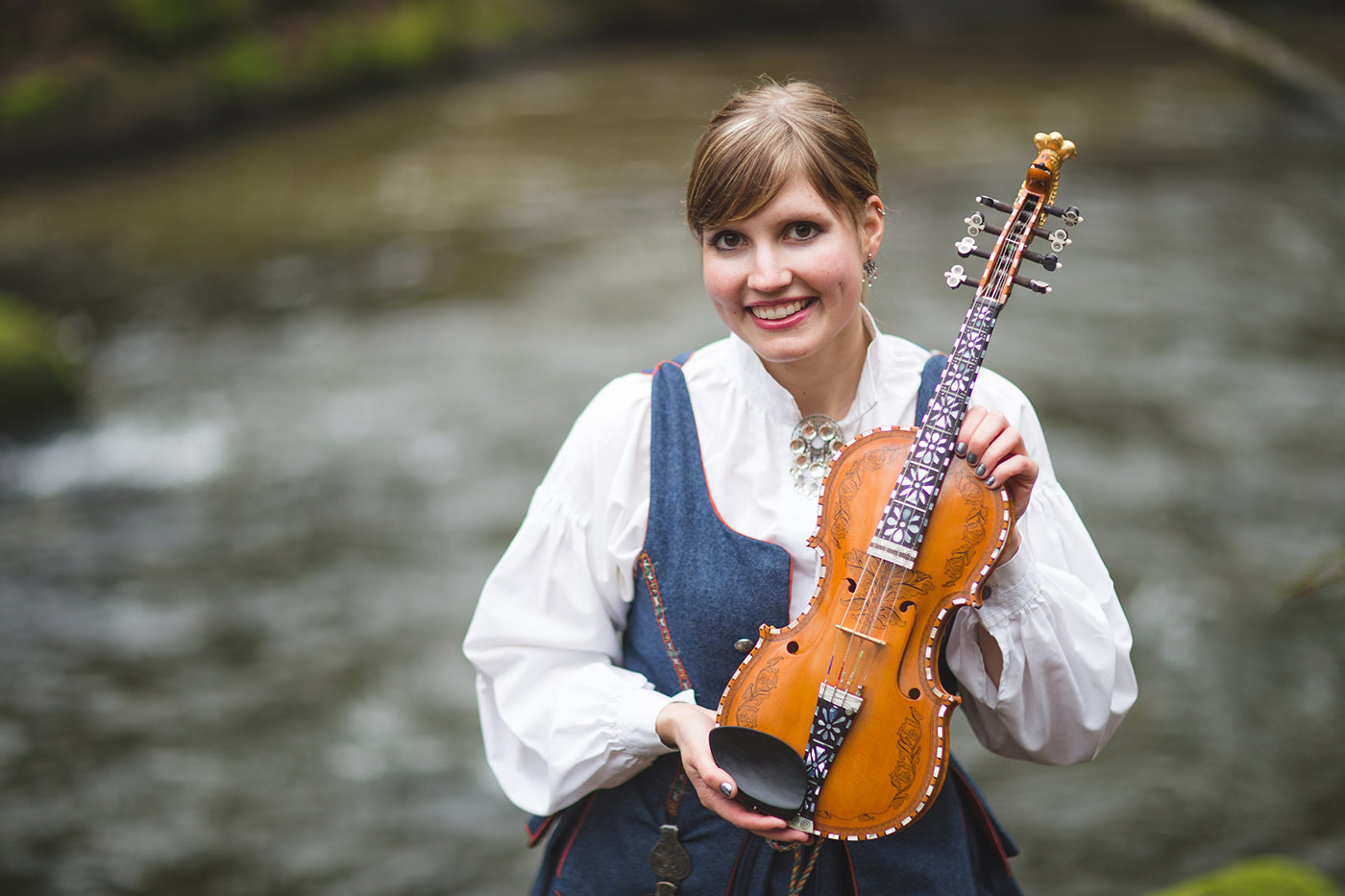 Rachel Nesvig in a traditional bunad holding her Hardanger fiddle