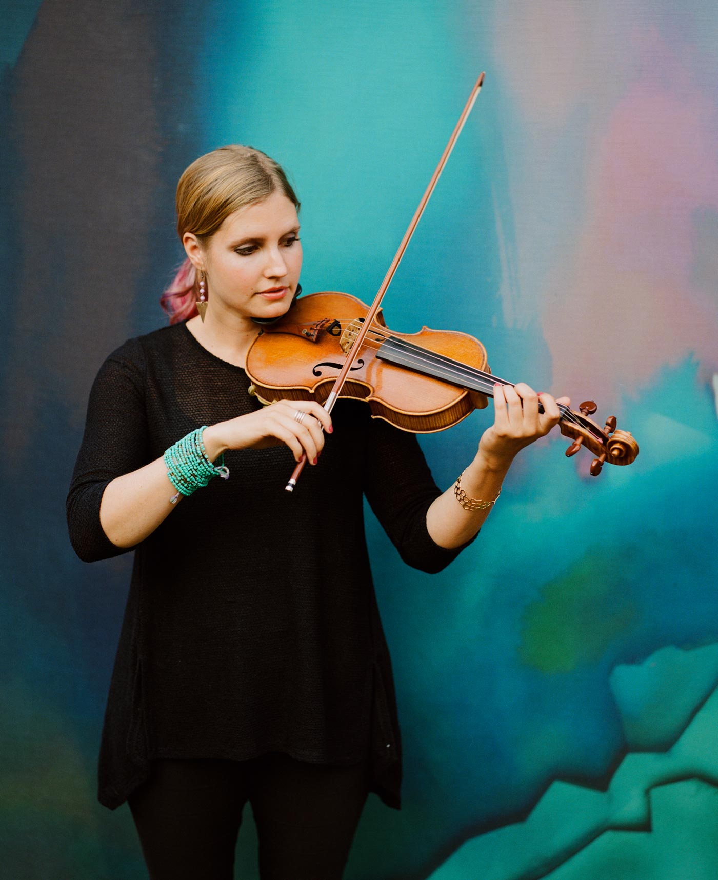 Rachel Nesvig playing violin in front of a colorful backdrop