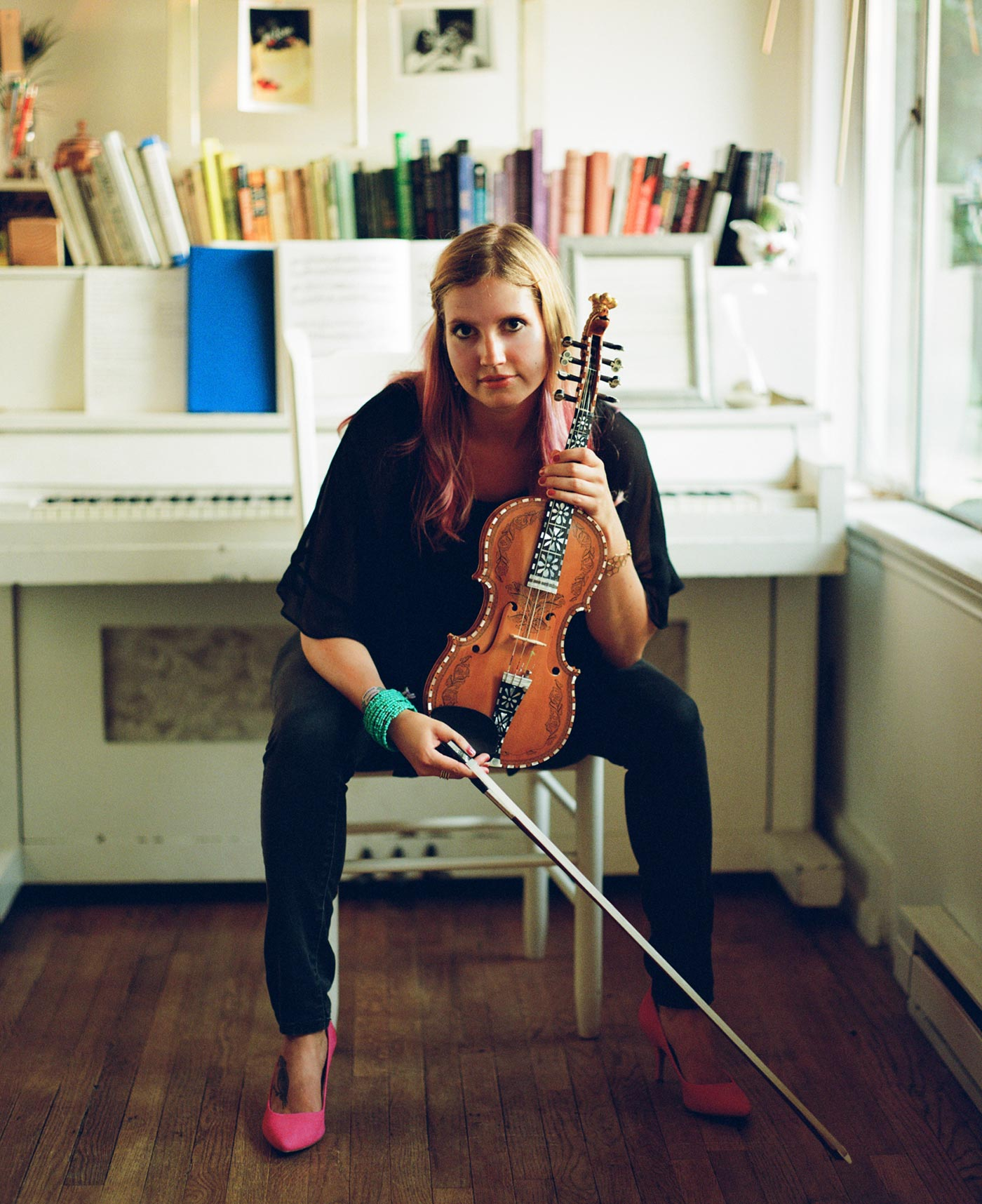 Rachel Nesvig holding a Hardanger fiddle and wearing pink shoes