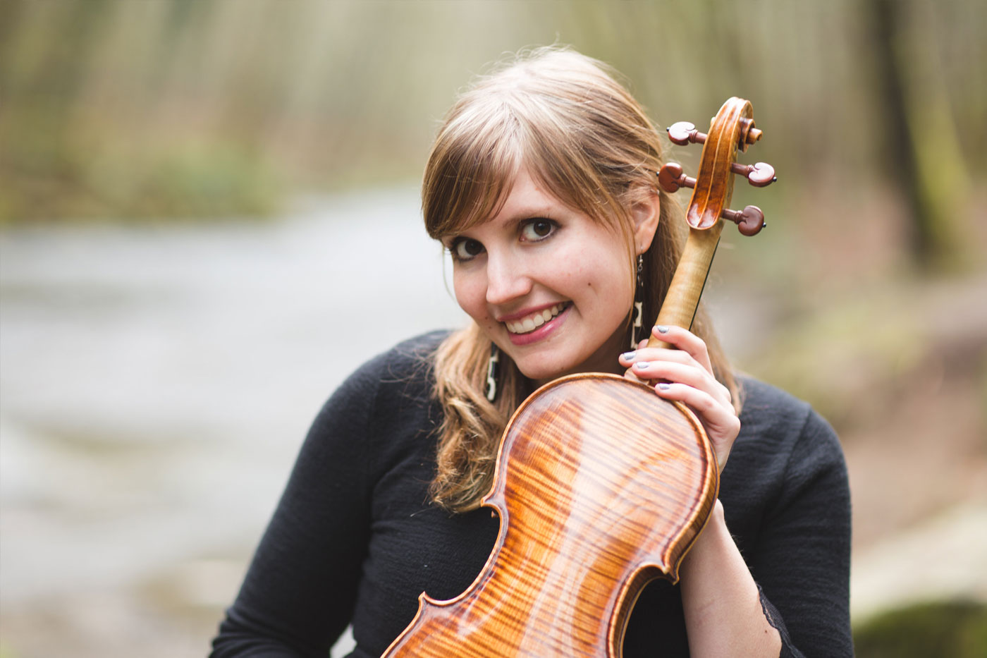 Rachel Nesvig with violin by a river