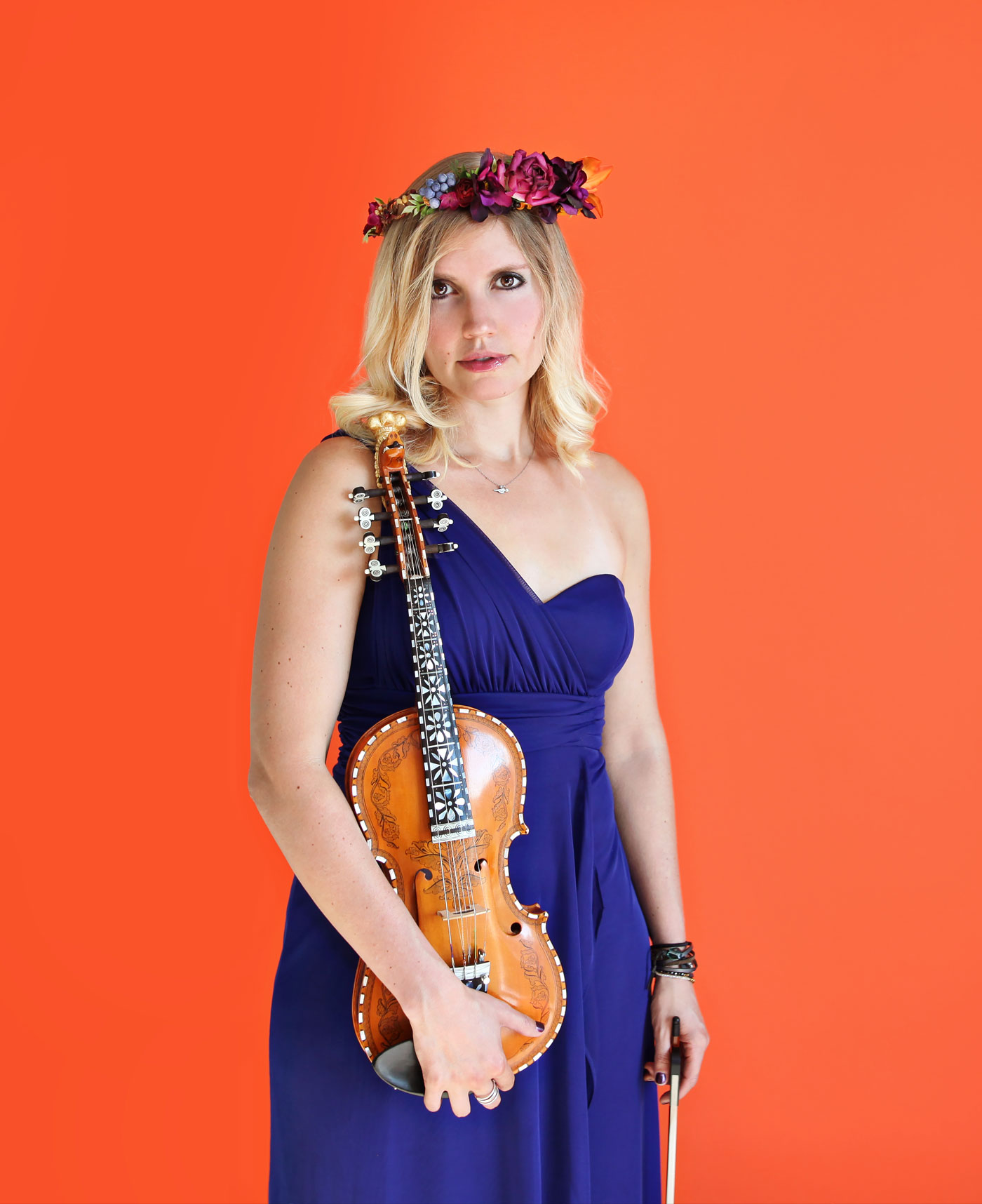 Rachel Nesvig wearing a blue dress on an orange background from 'High Right Now'