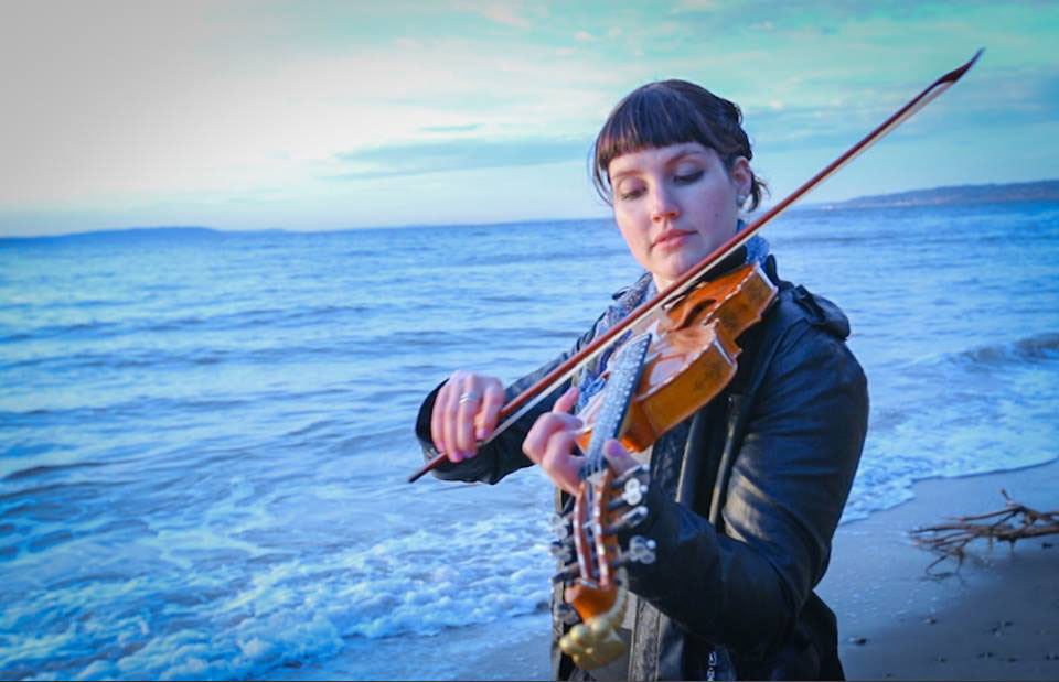 Rachel Nesvig playing Hardanger fiddle on the beach