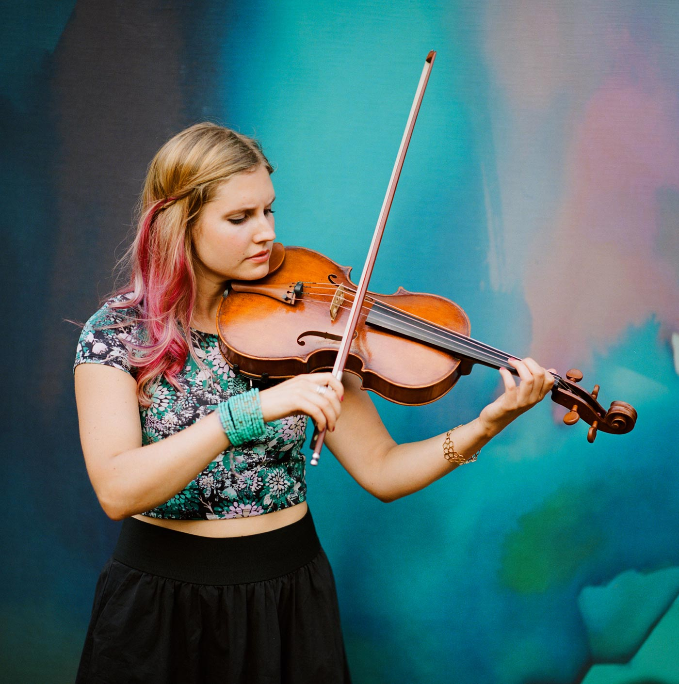 Rachel Nesvig playing viola in front of a colorful backdrop