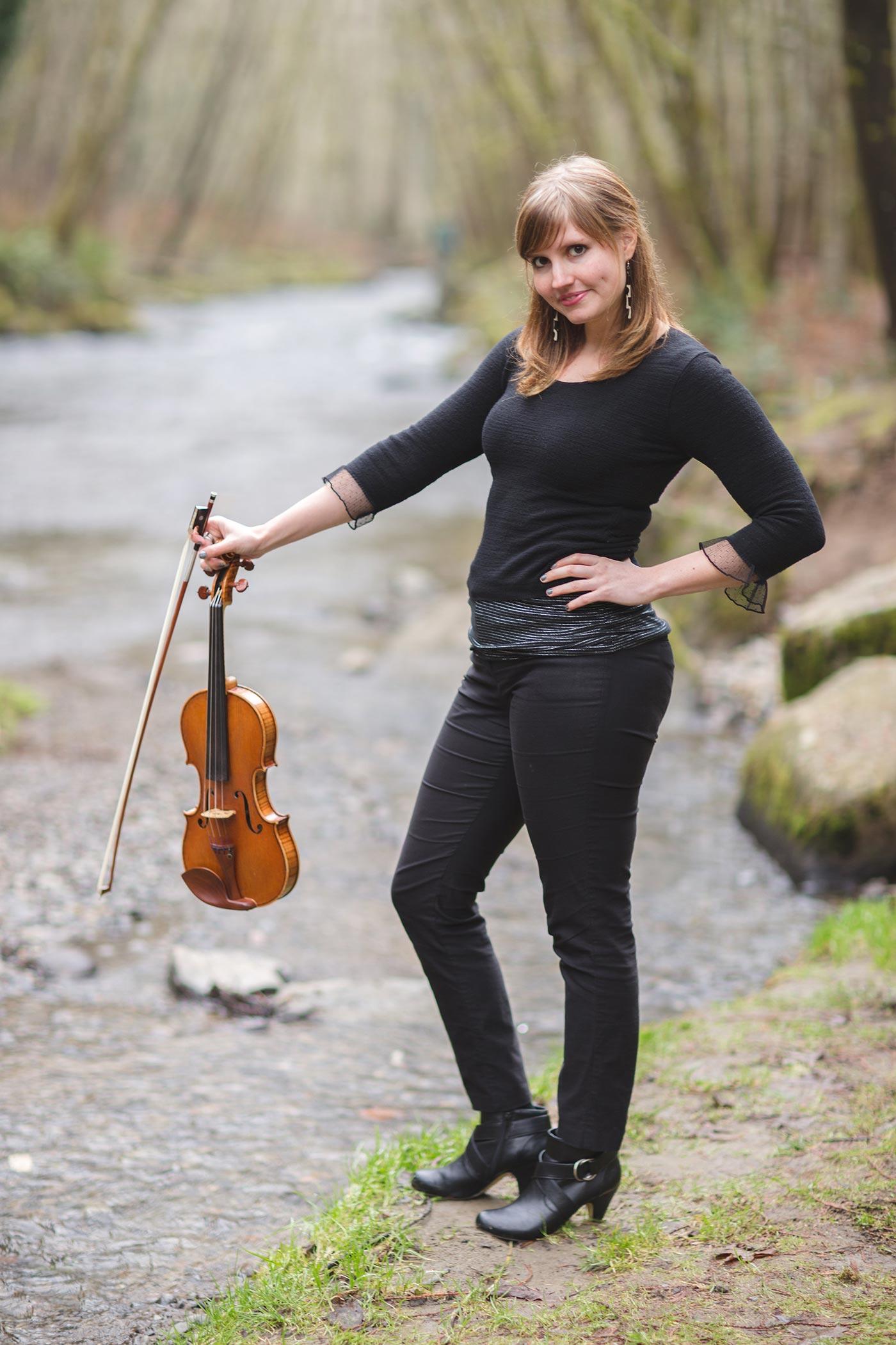 Rachel Nesvig holding a violin by a river